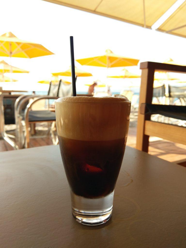 Pause am Strand mit dem Lieblingsgetränk der Griechen - eisgekühlter Café Crema