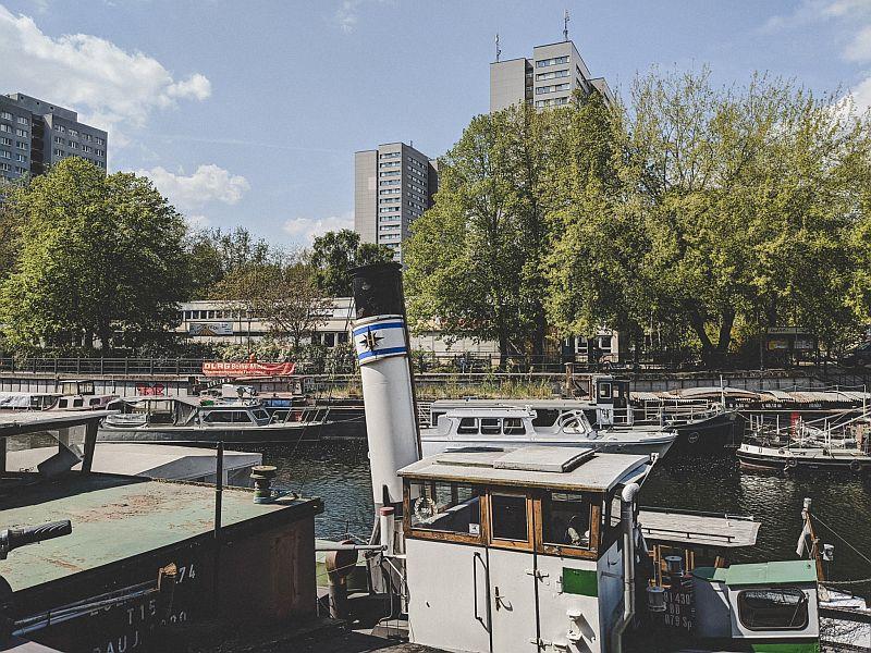 Der historische Hafen Berlin - Blick auf Plattenbauten und einen Schornstein
